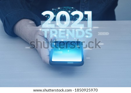 Glow lighting of phone in hands of guy. 2021 year trends in smartphone. Royalty-Free Stock Photo #1850925970