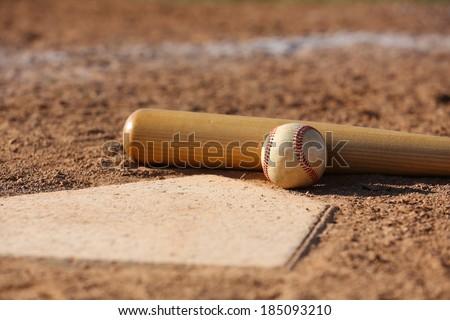 Baseball and Bat at Home Plate Close Up Royalty-Free Stock Photo #185093210