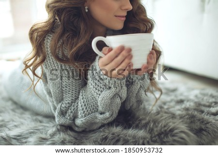 Close-up of female hands with a mug of drink. Beautiful girl in a gray sweater is holding a cup of tea or coffee in the morning sunlight. Mug for your design. High quality photo.