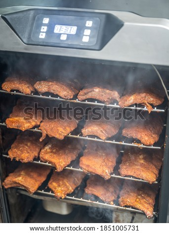 smoke rising around a slow cooked beef brisket on a smoker barbecue grilling concept Royalty-Free Stock Photo #1851005731