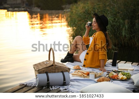 Young woman taking picture with camera on pier at picnic