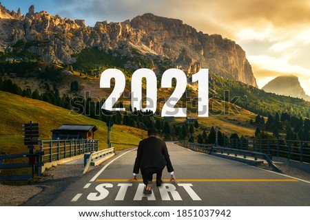 The 2021 New Year journey and future vision concept . Businessman traveling on highway road leading forward to happy new year celebration in beginning of 2021 for fresh and successful start . #1851037942