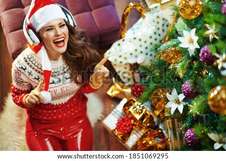Merry Christmas. Upper view of smiling elegant female in red sweater and Santa hat listening to the music with headphones near Christmas tree and gift boxes.