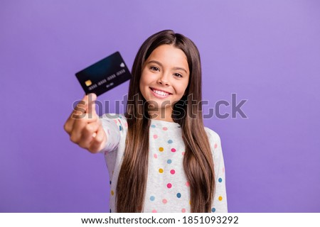 Photo portrait of smiling little girl with long brunette hair showing blurred debit card isolated on bright purple color background