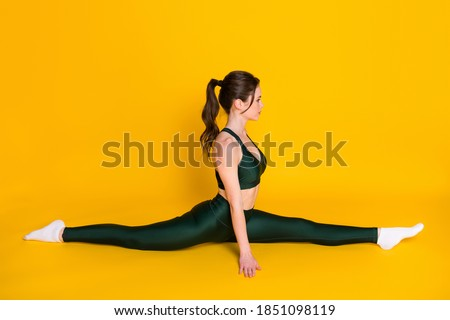 Photo of sportive lady practicing yoga sitting floor stretch split legs wear sports suit isolated yellow color background Royalty-Free Stock Photo #1851098119