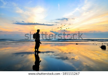 Silhouette of a photographer looking to the birds flying when sun rising up #185111267