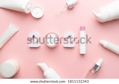 Best skincare products and cosmetic trends of 2021 concept. 2021 white number with lip balm, cream bottle, serum and lotion on pink background. Royalty-Free Stock Photo #1851132343
