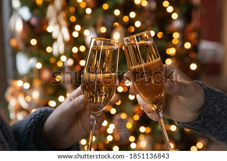 Crop close up of man and woman hold glasses with champagne clink greet congratulate with New Year. Couple celebrate Christmas winter holidays at home together, wish luck and joy. Celebration concept. #1851136843