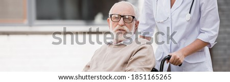 social worker walking with handicapped elderly man looking at camera, banner
