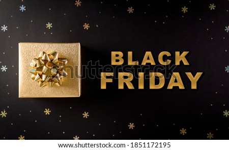 Top view of golden christmas gift boxes on black background with Black Friday text. Black Friday Sale, Banner, poster composition. #1851172195