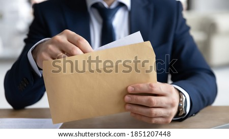 Close up young businessman entrepreneur in formal wear opening envelope with paperwork correspondence, male manager employee unpacking banking notification, law order or paper document at workplace. Royalty-Free Stock Photo #1851207448
