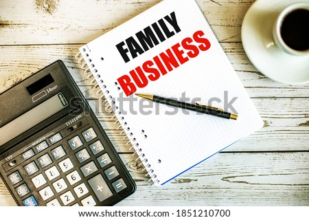 FAMILY BUSINESS written on white paper near coffee and calculator on a light wooden table. Business concept