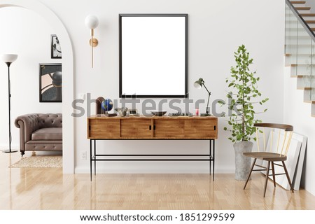 Stylish and eclectic dining room interior with mock up poster map, sharing table design chairs, gold pedant lamp and elegant sofa in second space. White walls, wooden parquet. Tropical leafs in vase. Royalty-Free Stock Photo #1851299599