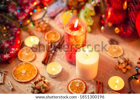 White and red burning candles on the table. Bright christmas decorations, warm colours cozy atmosphere, pleasant mood of the photo. Royalty-Free Stock Photo #1851300196