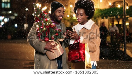 Portrait of happy smiling African American couple taking funny selfie photos on mobile phone on street with little christmas tree. Man and woman taking pictures at night on new years eve. Magic time