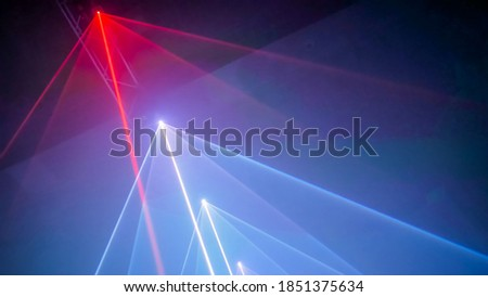 Interactive exposition in modern science museum or exhibition: bright laser show installation with color rays or beams in dark room. Performance, technology, visuals, digital, contemporary art concept Royalty-Free Stock Photo #1851375634