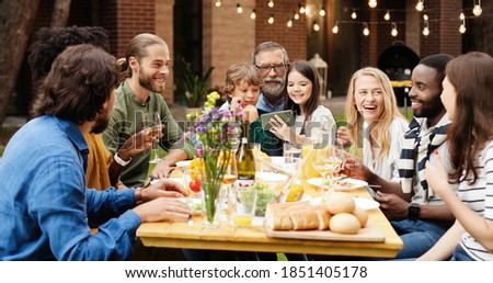 Happy multi ethnic family sitting at table with meal outdoor at picnic. Small kids sitting on grandfather knees and taking funny selfie photo on smartphone. Photos on mobile phone.
