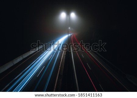 Horizontal photo of cars light trails on a curved highway at night with street lamps over the road. Motion blur image -  city road with traffic headlight motion (top view) in foggy and misty weather.  #1851411163