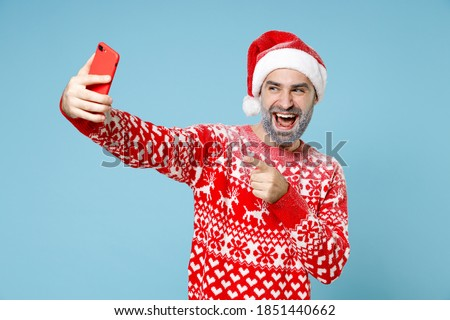 Funny Northern bearded man frozen face in Santa hat Christmas sweater doing selfie shot pointing index finger on mobile phone isolated on blue background. Happy New Year holiday winter time concept