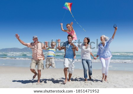 Full shot of a multi-generation family running with a kite on a sunny beach with the sea in background.