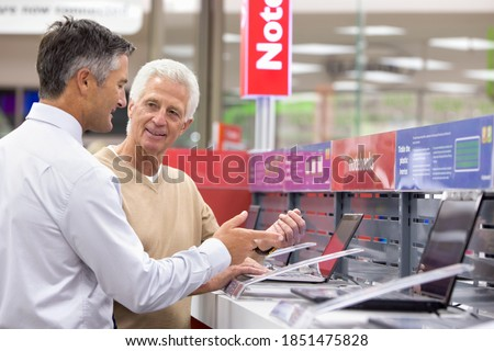 Medium shot of a salesman showing laptops to an elderly man in an electronics store. Royalty-Free Stock Photo #1851475828