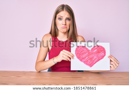 Young blonde girl sitting on the table holding heart draw depressed and worry for distress, crying angry and afraid. sad expression.