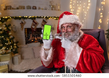 Happy Santa Claus sitting in chair near christmas tree and fireplace, showing mobile phone with green screen. Christmas spirit, holidays and celebrations concept