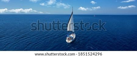 Aerial drone ultra wide panoramic photo of beautiful sailboat cruising the Aegean deep blue sea Royalty-Free Stock Photo #1851524296