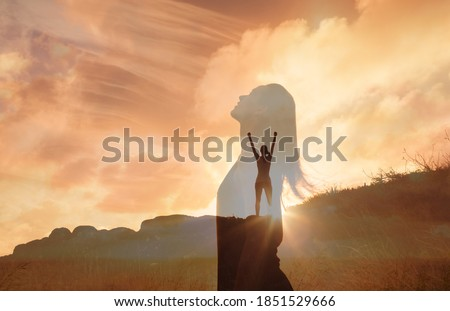 Woman celebrating on a mountain looking up to the sky. Letting go of all your mental fears. Hope, mental strength concept. Double exposure.