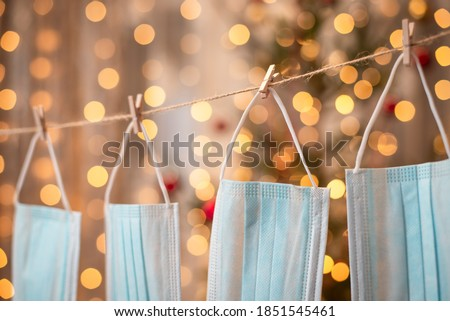 Close-up picture of four medical masks hanging on twine and creating garland. Warm yellow lights and christmas tree on the background.