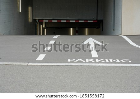 Entrance to underground parking in a modern residential building. The white painted lines separating the lanes and the word Parking with a big arrow show the direction to drive in safety.