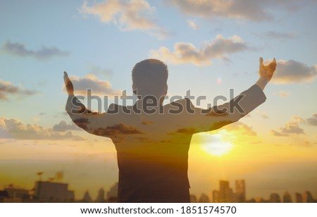 Double exposure of confident young businessman lifting his arms up to the sunrise sky facing the city. Religious belief, people feeling inspired and motivated concept.  Royalty-Free Stock Photo #1851574570