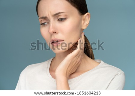 Closeup of sick sad woman checking lymph nodes, caught cold, suffering from throat problems, isolated on studio blue background Royalty-Free Stock Photo #1851604213