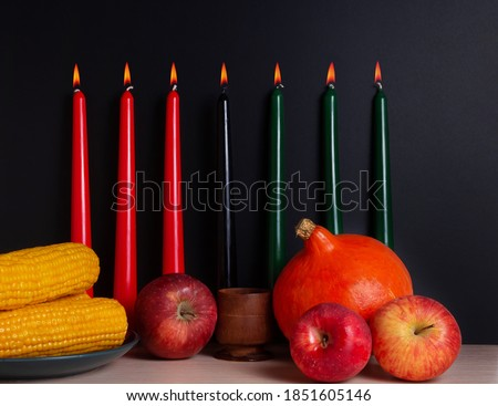 Kwanzaa banner with candles on light background and copy space on the right. Afro-American holiday. Seven candles as symbol of principles of African Heritage.