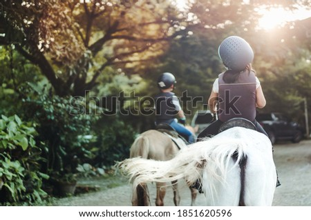 Horse rider.Back view Kids learn to ride a horse.Happy asian kid girl riding horse in horse school farm club.Horseback riding, lovely powerful equestrian.Cowgirl kid fun in farm.Kids Activity.Animals.