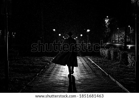 dark silhouette of a male detective in a coat and hat in the rain on a night street in the style of Noir Royalty-Free Stock Photo #1851681463