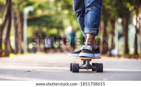 Closeup Asian man playing on surfskate or skate board in outdoor Park when sunrise time over photo blur of unrecognized people running, extream sport, healthy and exercise, fashion in covid19 concept