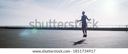 Fit young man skipping with a jump rope outdoors. Male athlete doing fitness training in morning. Workout during lockdown outside the gym. Royalty-Free Stock Photo #1851734917