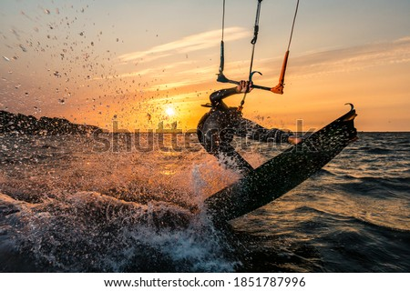 Flash photo of kitesurfer in beautiful yellow sunset at the baltic sea