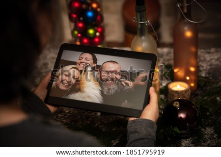 a woman is having a video conference at home with a group of friends, chatting with a tablet, concepts like holidays during social distancing, corona virus or covid 19 during christmas #1851795919