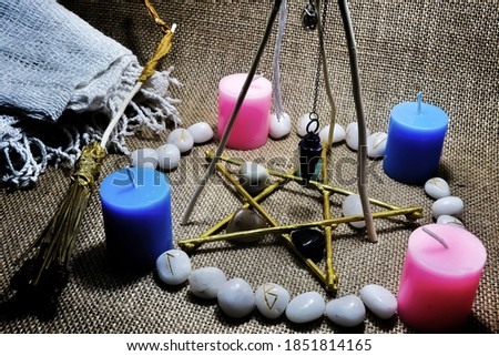 Pentacle and pendolum spellings, with runes surrounding them placed on sackcloth, composed of colored candles. This picture is suitable for witchcraft writing.