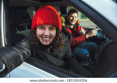 couple in rent car smiling woman in red winter hat