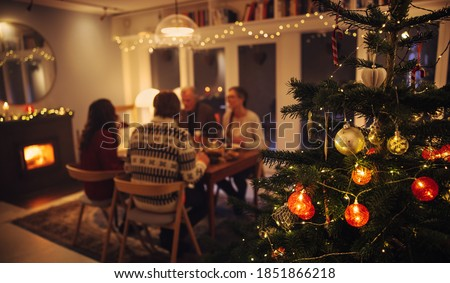 Interior shot of warm cozy Christmas decorated family home. Family sitting at dinner table having a Christmas eve dinner together. #1851866218