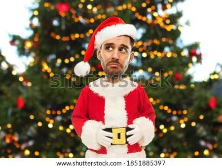 emotion, expression and winter holidays concept - sad man in santa claus costume over christmas tree background (funny cartoon style character with big head)