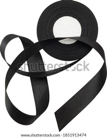 Black silk ribbon reel isolated on white background. Black Ribbon Spool. Silk satin black ribbon isolated background. Loose black ribbon Royalty-Free Stock Photo #1851913474