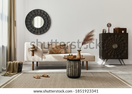 Interior design of ethnic living room with modern commode, round mirror, decoration, furniture and personal accessories. Template. White wall. Royalty-Free Stock Photo #1851923341