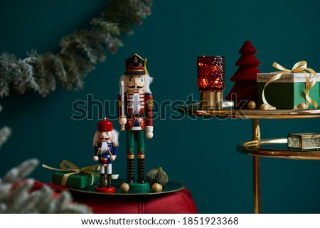 Christmas composition on the red velvet bench with decoration, gifts, wreath, nutcracker and accessories. Copy space. Red and green color. Template.  Royalty-Free Stock Photo #1851923368