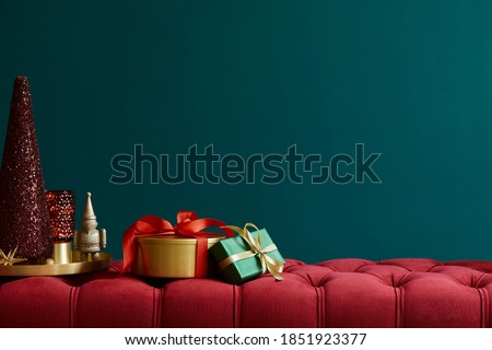 Christmas composition on the red velvet bench with decoration, gifts, wreath, lantern and accessories. Copy space. Red and green color. Template.  Royalty-Free Stock Photo #1851923377