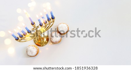 Image of jewish holiday Hanukkah with menorah (traditional Candelabra), donut and wooden dreidel (spinning top)