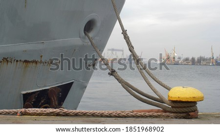 Moored Ship Swinging on Waves Moving Mooring Ropes Up and Down on Bollard Royalty-Free Stock Photo #1851968902